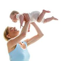 Junge Mutter macht mit ihrer 6 Monate alten Tochter Rueckbildungsgymnastik, isoliert vor weissem Hintergrund. Sie kniet am Boden und hebt das Baby hoch und lacht dabei.